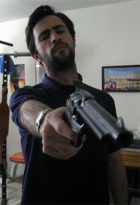 Mark Mushakian with gun and scruffy face