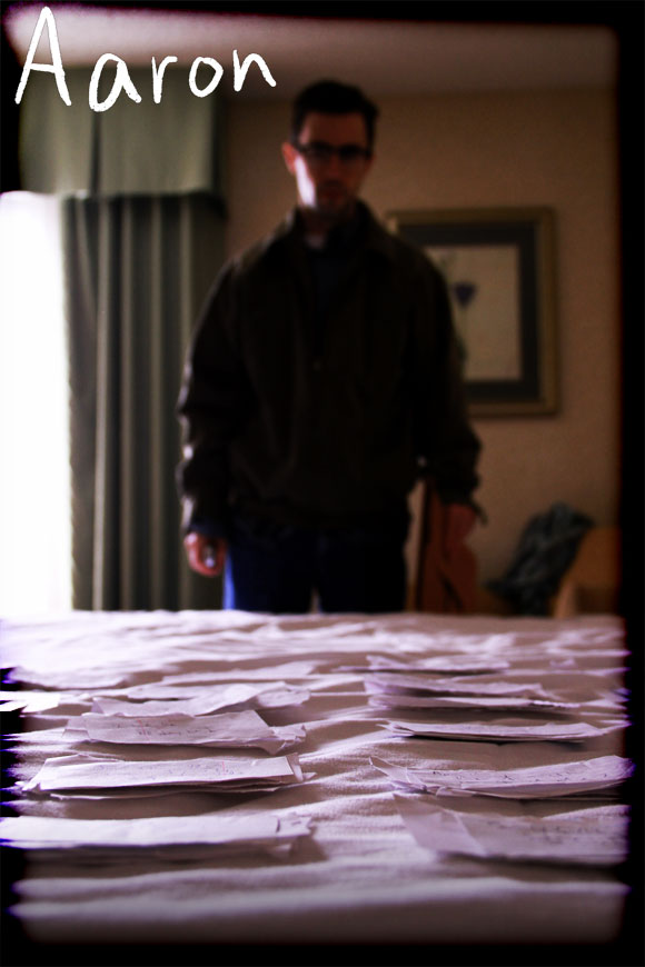 production still from Aaron, poster style standing over notes on bed