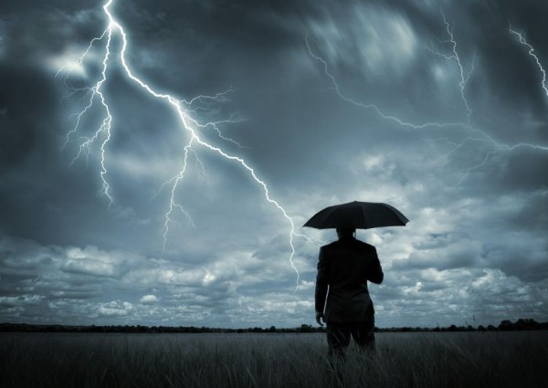 man with umbrella in lightning storm
