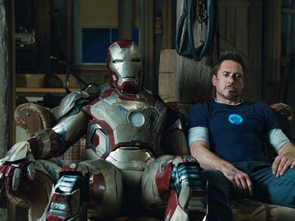 Robert Downey Jr as Tony Stark on couch with Iron Man suit in 3