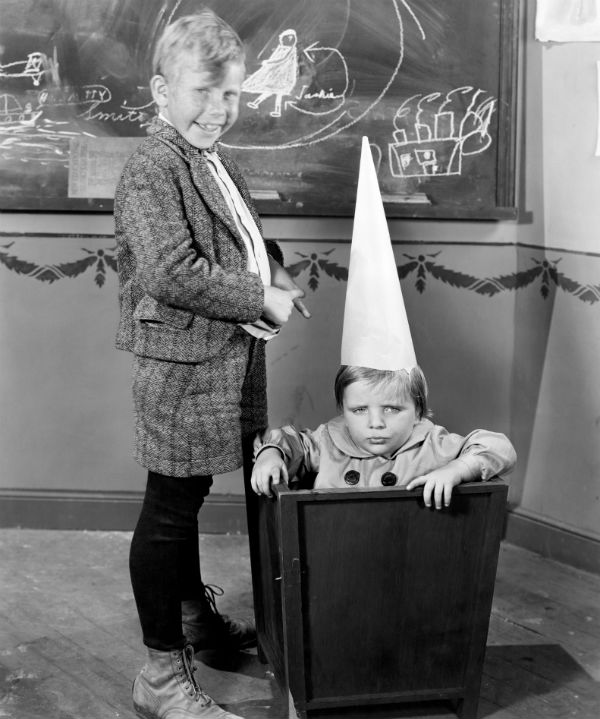 Old time child wearing dunce cap and sitting in bucket