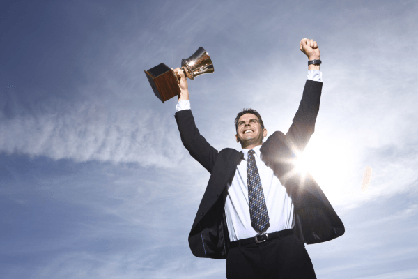 cheesy success stock photo business man victory holding trophy