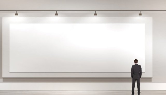 man standing in front of large blank canvas on wall