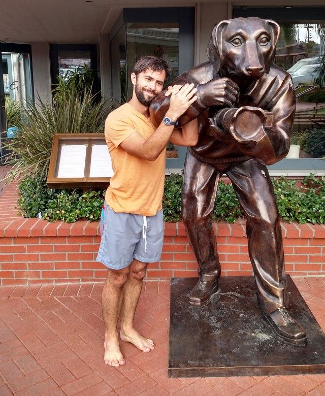 Mark Mushakian with dog statue in La Jolla